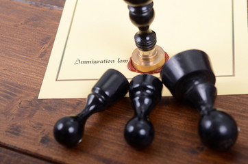 Notary seals and Immigration law on the wooden background.