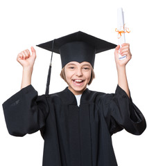 Emotional portrait of a graduate little happy girl student in a black graduation gown with hat, holding diploma, isolated on white background. Lucky cheerful schoolgirl celebrating triumph.
