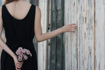 Anonymous female with bouquet near wooden wall
