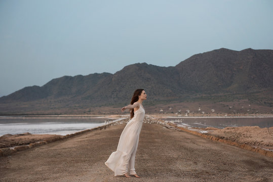 Side view of young woman standing on dirt road against mountain