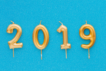 Happy new year 2019. Gold shiny number, candles on colored background. Christmas , festive background.