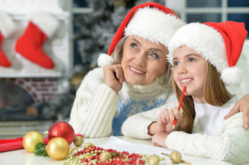 Portrait of happy grandmother with girl preparing for Christmas