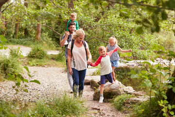 Family Hiking Along Path By River In UK Lake District Wall mural