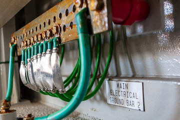 Green electrical ground wires is connected to ground copper terminal bar or earth bonding terminal bar in electrical device and electrical grounding sign near ground bolt for safety system.