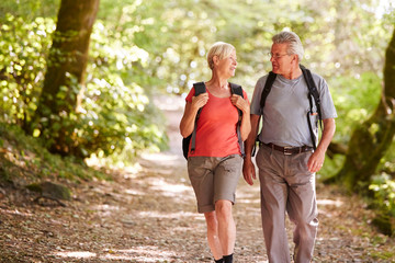 Senior Couple Hiking Along Woodland Path In Lake District UK Together Wall mural