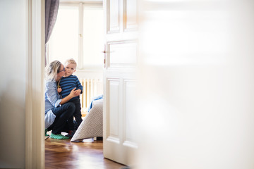 Young mother kissing her toddler son inside in a bedroom. Copy space. Wall mural