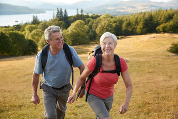Senior Couple Climbing Hill On Hike Through Countryside In Lake District UK Together