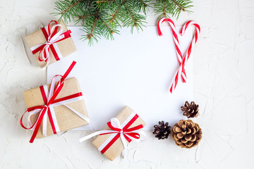 Clear paper laying with candy cane, Christmas tree branches and gifts