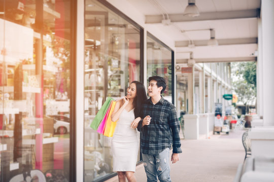 Young asian couple enjoy walking shopping at outlet mall.