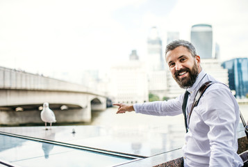 Hipster businessman standing by the river in London, pointing at seagull.