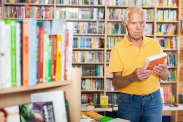 Portrait of senior man visitor looking intresting book