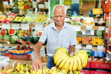 Portrait of smiling older man choosing sweet ripe fruits in farmer market