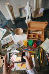 Sharing photos with art work on internet. Hand are holding phone and taking pictures of art work. Artists desk table top view from above. Vertical composition