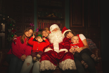 Christmas family portrait in a festive living room with a real Santa Claus.