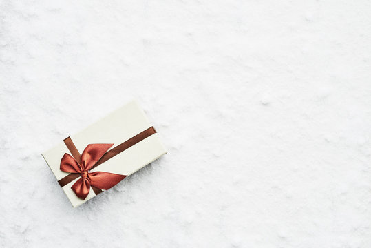 Top view of wrapped Christmas gift box with maroon ribbon on the snow. Copy space for text.