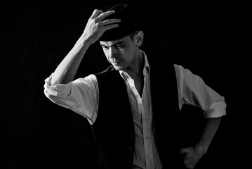Portrait of an old-fashioned man in a white shirt with suspenders and a cylindrical hat. Isolated on dark background