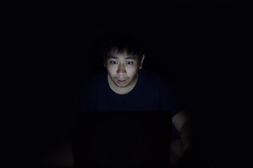 Asian man using laptop in the black dark room and show surprise something on his face