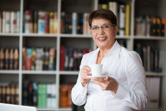 Portrait of  senior businesswoman wearing glasses head shot in a white shirt, crossed hands looking at the camera with a warm friendly smile against the background of a bookcase