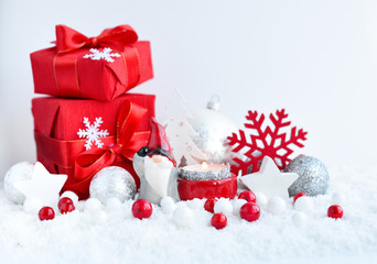 Christmas composition with with a candle, gifts and festive decorations оn the snow. Christmas or New Year greeting card.