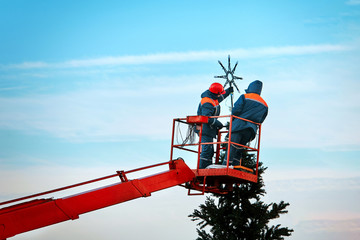 Workers on the crane bucket instaliing topper on Christmas tree in the city. Worker hang star. Preporation for New year celebration. Christmas light installation & decorating services..Work at height Fotomurales