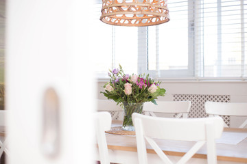 cozy dining room interior with flower decoration in a white room of a modern house close-up