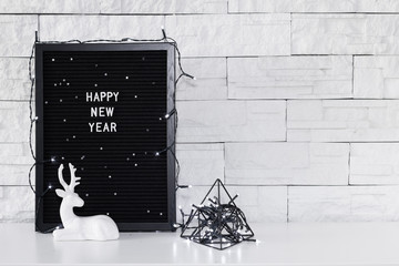 Happy new year text message on the dark board, figurine of a deer and black holidays decorations on the white background
