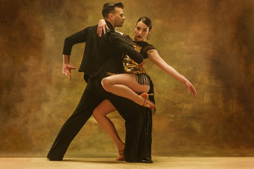 Foto op Canvas Dance School The young dance ballroom couple in gold dress dancing in sensual pose on studio background. Professional dancers dancing tango. Ballroom dance concept. Human emotions - love and passion