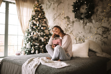 Dark-haired girl dressed in white sweater and pants holds a New Year gift in her hands sitting on the bed with gray blanket and white pillows in a decorated room with a New Year tree and candles