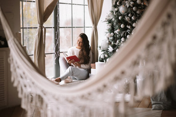 Nice dark-haired girl dressed in pants, sweater and warm slippers reads a book sitting on the windowsill of a panoramic window in the room with hammock next to the New Year tree and gifts