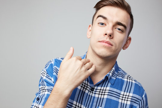 Self Confident guy dressed in a plaid shirt is on a white background in the studio