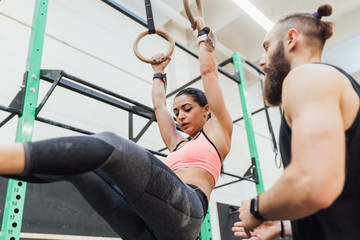 young man and woman training toghether indoor gym gymnastic rings - crossfit, sportive, training concept