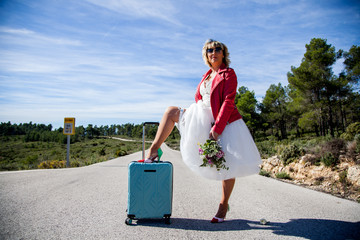 A woman dressed as a bride, with a red jacket, a bouquet and a leg resting on a suitcase, poses in the middle of a lonely road.