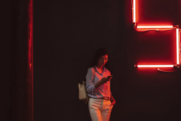 Beautiful elegant Thai woman standing at night club by the red neon light and typing on her cell phone.