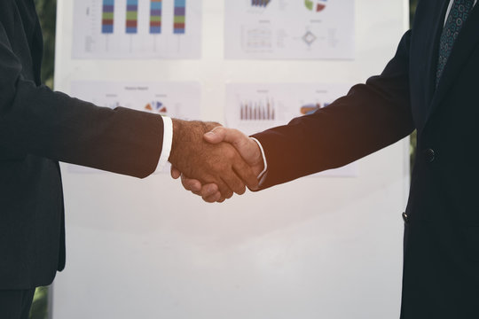 businessmen with partner shaking hand after agreement complete