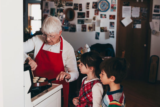 Grandmother cooking traditional Swedish Christmas dumplings with her grandchildren