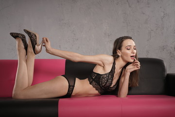 beautiful slim lady wearing black lace lingerie set and posing on the leather sofa alone