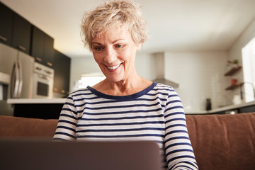 Senior white woman using laptop computer at home, close up