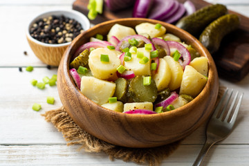 Potato salad with pickled cucumbers and onion in bowl on white wooden table. Selective focus.