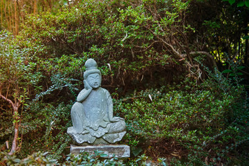 A weathered stone statue of a Buddha or Buddhist monk sitting and observing world, meditates under green trees in japanese garden. Relax and mind calm concept. Exterior,outdoor decor. Copy space.