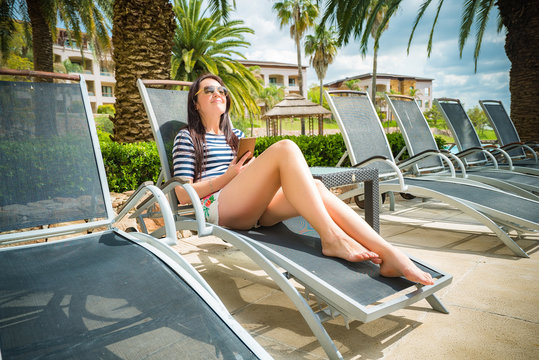 Woman on a lounger by the pool with mobile phone