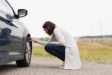 Woman checking car tyre during breakdown