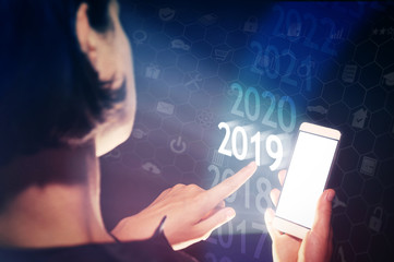 Woman select 2019 on her smartphone. New year in high tech.