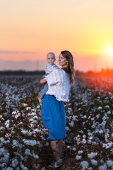Mother and baby in a cotton field at sunset