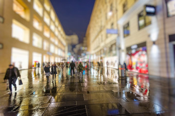 crowd of people walking on the night rainy streets in the city