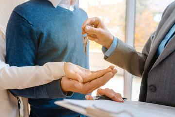 Maklerin oder Vermieter übergibt die Wohnungsschlüssel