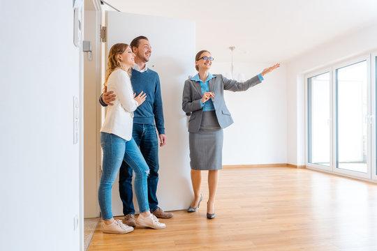 Maklerin und junges Paar auf einer Wohnungsbesichtigung