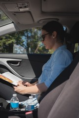 Woman reading a book in a car