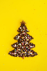 Winter composition with Christmas tree made by coffee beans and decorated anise star, cinnamon stick and multicolored culinary sprinkling on a yellow background, flat lay.