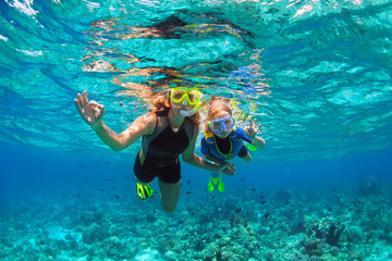 Happy family - mother, kid in snorkeling mask dive underwater with tropical fishes in coral reef sea pool. Show by hands divers sign OK. Travel lifestyle, beach adventure on summer holiday with child.