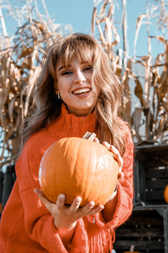 Young woman on a pumpkin farm. Beautiful girl near pumpkins. A girl with a pumpkin. Pumpkin Field. Europe farm.